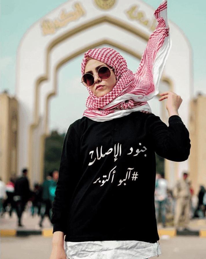 Iraqi woman with black top with Arabic writing