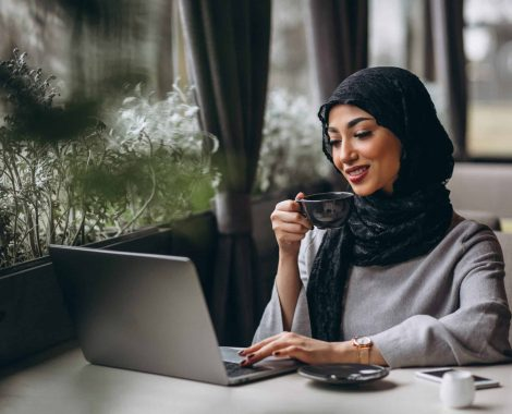 woman in hijab inside a cafe working on laptop