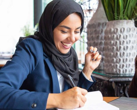 Young woman in hijab writing in notebook and laughing.